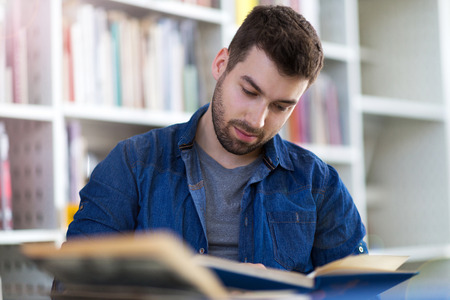 Young male student studying in the library