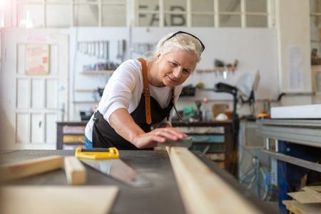 Senior woman doing woodwork in a workshop Archivio Fotografico