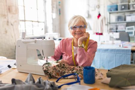 Pewna siebie starsza projektantka mody w swoim warsztacie