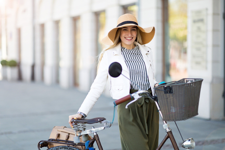 Attractive young woman standing with her bicycle in the city