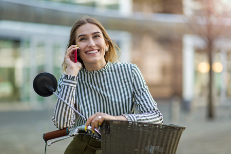 Young woman On Bike Using Mobile Phone Stock Photo