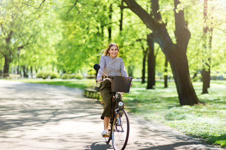 Attractive young woman cycling through the park