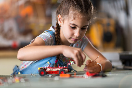 Small girl making a robot