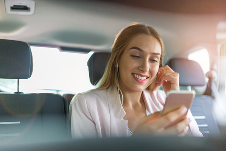 Young woman on the back seat with smart phone