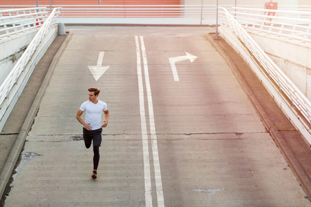 Young man running in urban area Stock Photo