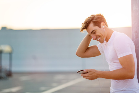 Sportive young man in the city with smartphone Stock Photo