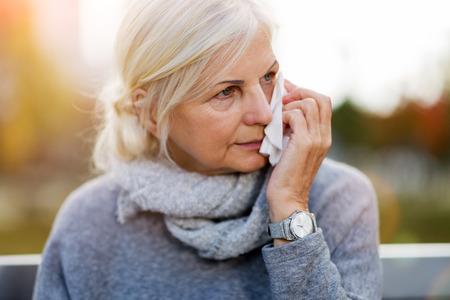 Une vieille femme qui pleure s'essuie les yeux avec un mouchoir en papier Banque d'images