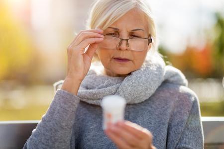 Hogere vrouw die etiket op medicatie controleert