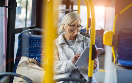 Senior woman using a tablet, while riding public bus