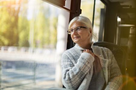 Senior vrouw kijkt door het raam tijdens het reizen in de bus Stockfoto