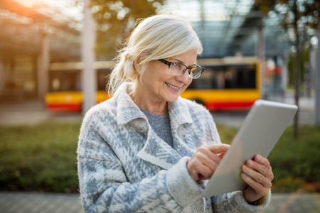 Senior woman using tablet, while waiting for the bus