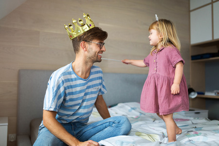 Daughter casting spell on father with magic wand Stock Photo