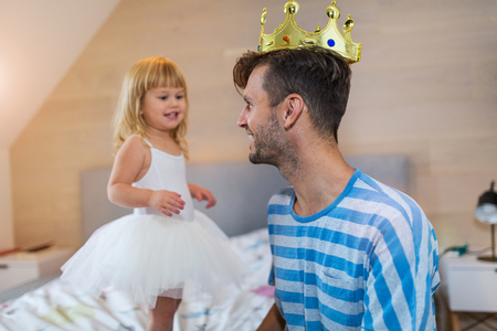 Little girl putting a golden crown on dads head