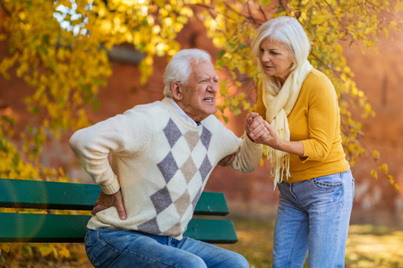 Senior woman helping a senior man who has a back pain