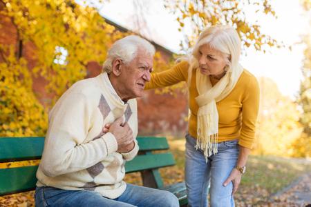 Senior man experiencing chest pain while senior woman comforts him