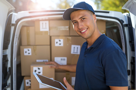 Livreur souriant debout devant sa camionnette Banque d'images