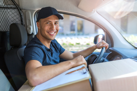 Smiling delivery man with boxes in his van Stock Photo