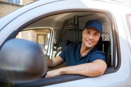 Lächelnder Lieferbote, der in seinem Lieferwagen sitzt