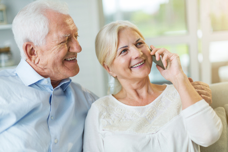 Senior couple talking on mobile phone at home 免版税图像