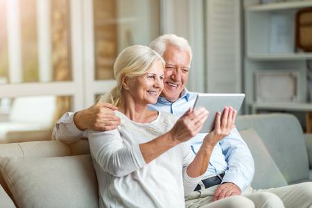 Coppia senior utilizzando tablet digitale a casa