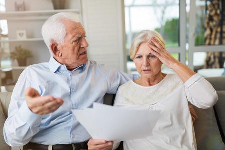 Las parejas ancianas mirando a través de facturas
