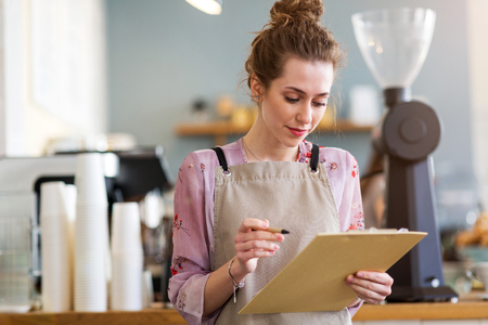 Woman working in coffee shop Imagens