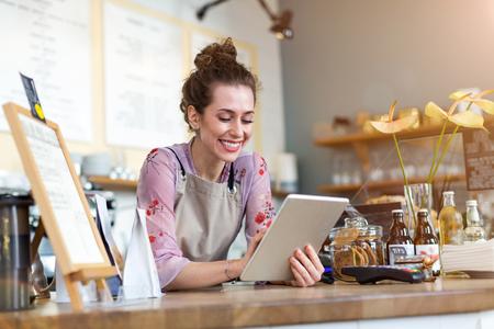 Jonge vrouw met behulp van een digitale tablet in een coffeeshop Stockfoto