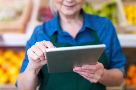 Vendeuse avec tablette numérique dans une petite épicerie