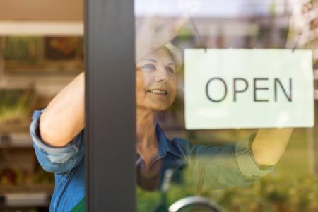 Senior woman holding an open sign in boutique de produits biologiques