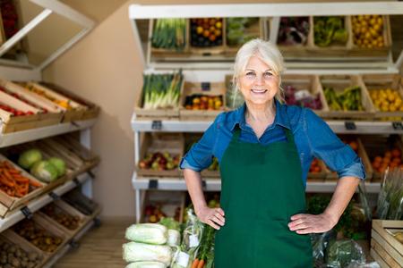 Mujer mayor que trabaja en la pequeña tienda de comestibles
