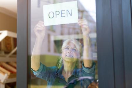 Senior vrouw met een open bord in de winkel voor biologische producten Stockfoto