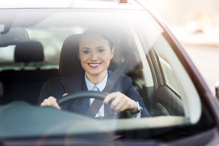 Happy woman driving a car and smiling Stock Photo