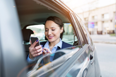 Businesswoman with phone on the back seat of a car Stockfoto
