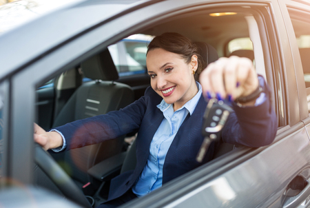 Young businesswoman sitting in car holding car keys
