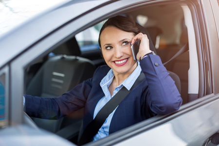 Woman using smartphone while driving a car