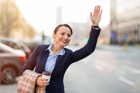 Woman waving for a taxi on city street Imagens