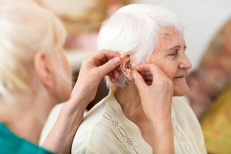Female doctor applying a hearing aid to a senior woman's ear