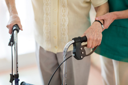 Nursing assistant helping senior woman with walking frame Imagens