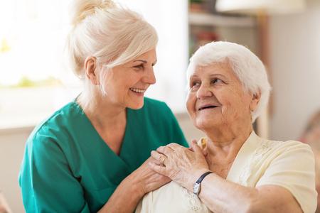 Ältere Frau mit ihrer weiblichen Pflegekraft Standard-Bild