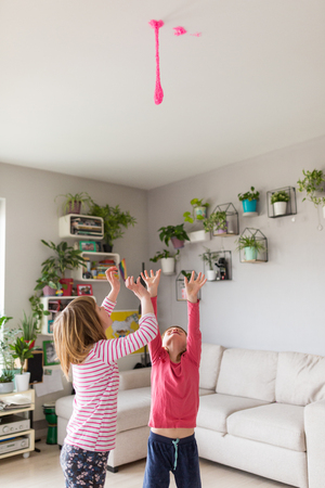 Little girls playing with slime toy hanging from the ceiling