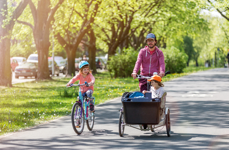 Father and daughters having a ride with cargo bike during spring Stockfoto