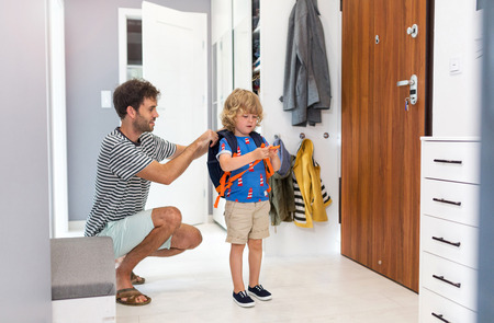 Father helping son get ready for school