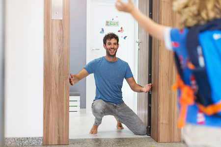 Little boy running towards his father waiting for him at home
