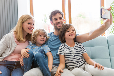 Family taking selfie while sitting on sofa at home