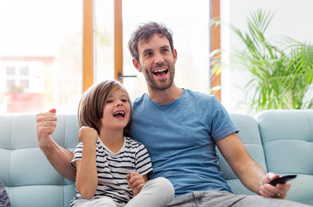 Father and son watching television on sofa