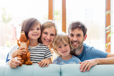 Happy young family with two children at home