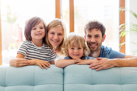 Felice giovane famiglia con due bambini a casa