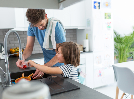 Boy helping father in kitchen