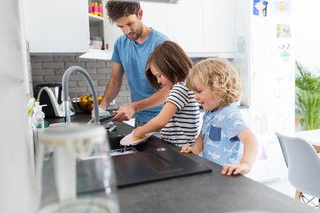 Children helping father in kitchen