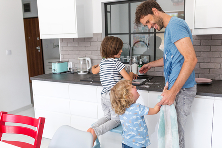 Children helping father in kitchen